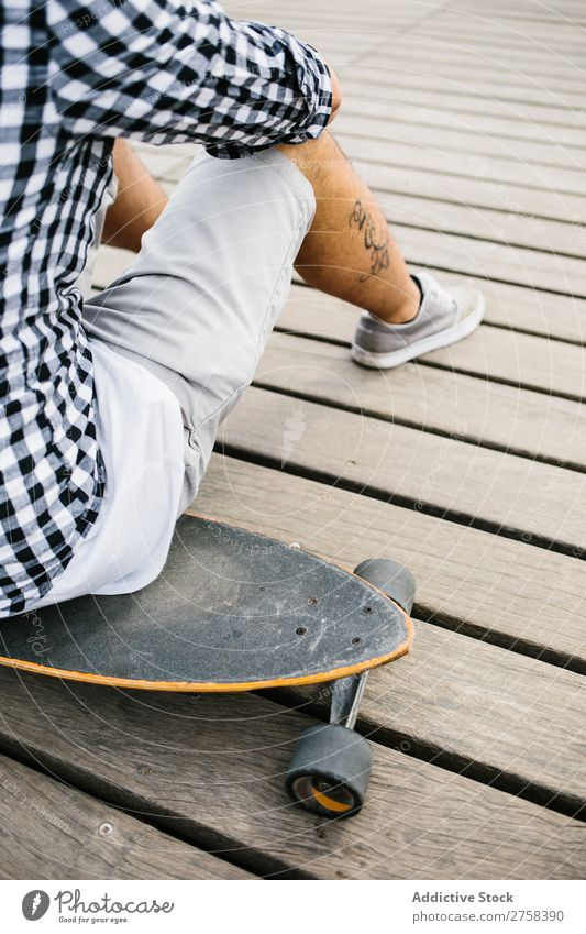 Tattooed man sitting on skateboard Man skateboarder Sit Skateboard Ice-skates Town Sports Skateboarding Youth (Young adults) Board Ice-skating Human being