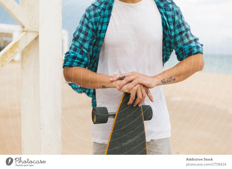 Man in summer apparel holding skateboard on sandy beach. Skateboard Coast Beach Leisure and hobbies Summer Multicoloured youngster Action Youth (Young adults)