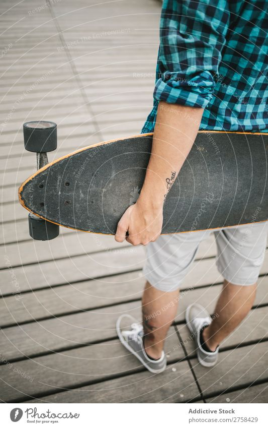 Man with tattoos holding skateboard at shore. Back view. Skateboard Coast Beach Leisure and hobbies Summer Multicoloured youngster Action Youth (Young adults)