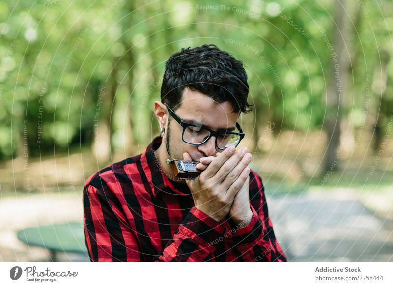 Man playing mouth organ Musician harmonica Face Human being instrument Lifestyle Loneliness Park Youth (Young adults) Guitar solo eyes closed Organ Mouth