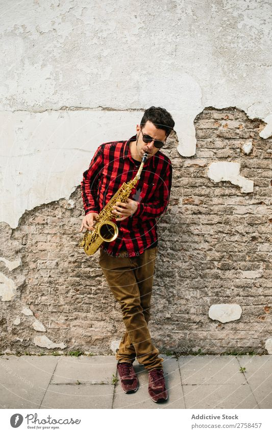 Smiling jazzman with sax Musician Man Sunglasses Self-confident Cool (slang) Cheerful Wall (building) Youth (Young adults) Jazz Saxophone instrument Musical