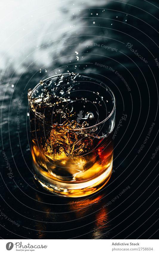Glass of splashing whiskey Alcoholic drinks Beverage Bourbon Brown Cocktail Cold Cool (slang) Crystal Cube Dark Drinking Drop Elegant Bird's-eye view glassware