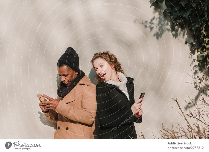 Couple in warm clothes with smartphones multiethnic Style Street PDA using Stand Easygoing Beautiful Mixed race ethnicity Black Youth (Young adults) Together