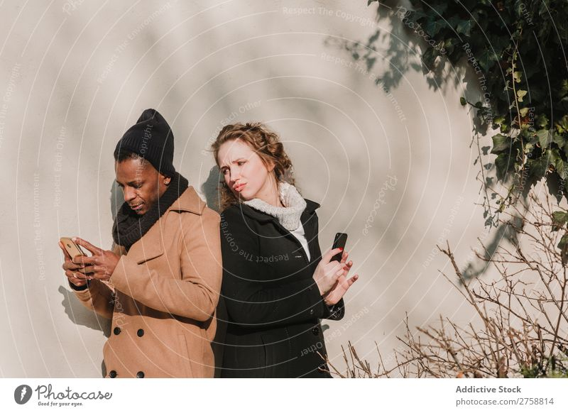 Couple in warm clothes with smartphones Style Street PDA Stand Easygoing Beautiful Mixed race ethnicity