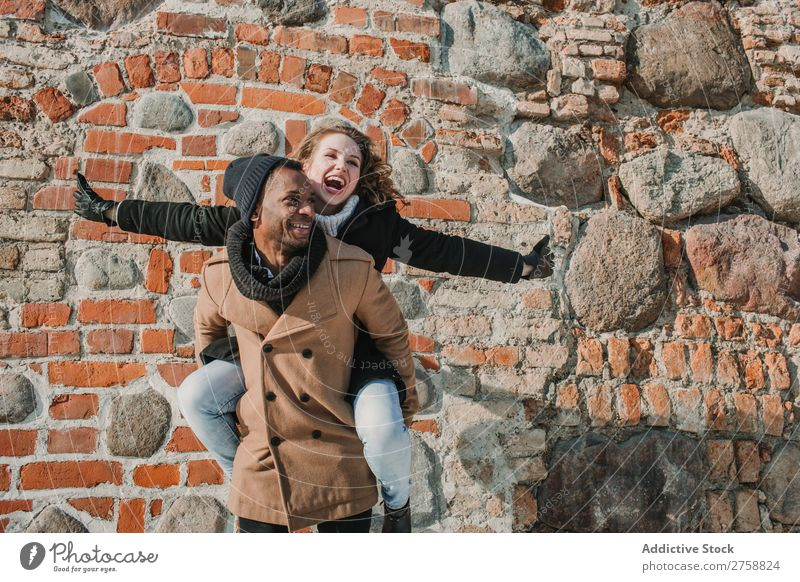 Couple having fun at brick wall multiethnic Style Street warm clothes Easygoing Brick Wall (building) Carrying on back Stone piggyback Beautiful