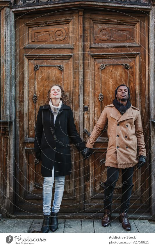 Couple holding hands at vintage door multiethnic Style Street warm clothes eyes closed Wood Door grungy Old Easygoing Beautiful Mixed race ethnicity Black