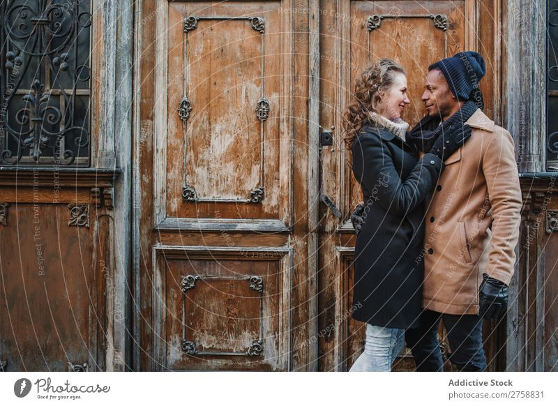 Couple embraced at vintage door multiethnic Style Street warm clothes Wood Door grungy Old Easygoing Beautiful Mixed race ethnicity Black Youth (Young adults)