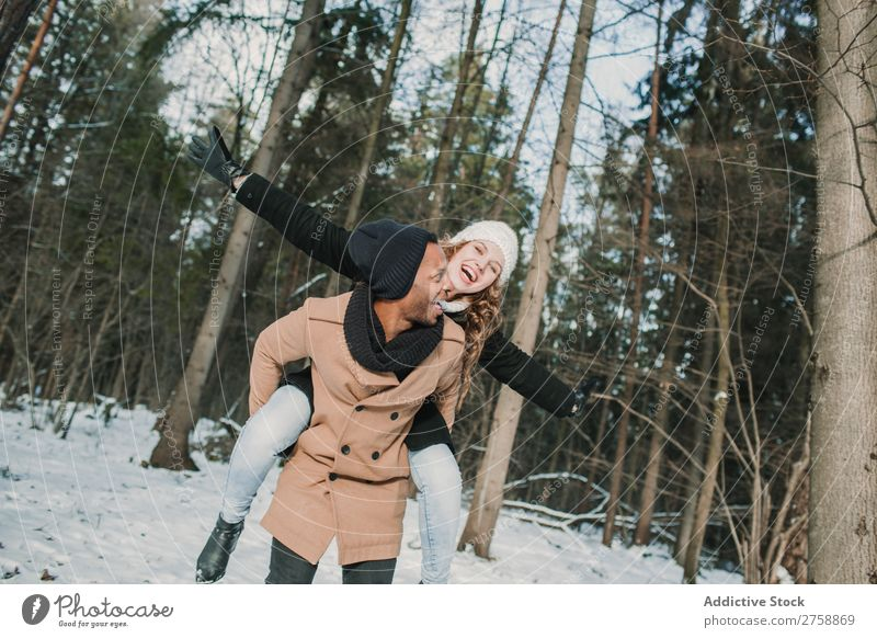 Couple having fun in winter forest multiethnic Style warm clothes Easygoing Nature Forest Winter Snow piggyback Beautiful Mixed race ethnicity Black