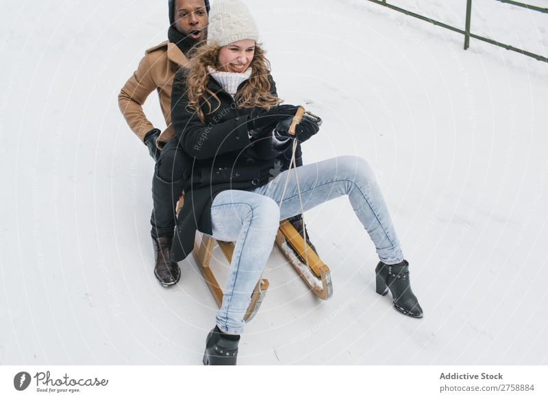 Couple riding sledge on snowy hill multiethnic Style warm clothes Easygoing Nature Sledge Winter Snow Beautiful Mixed race ethnicity Black Youth (Young adults)