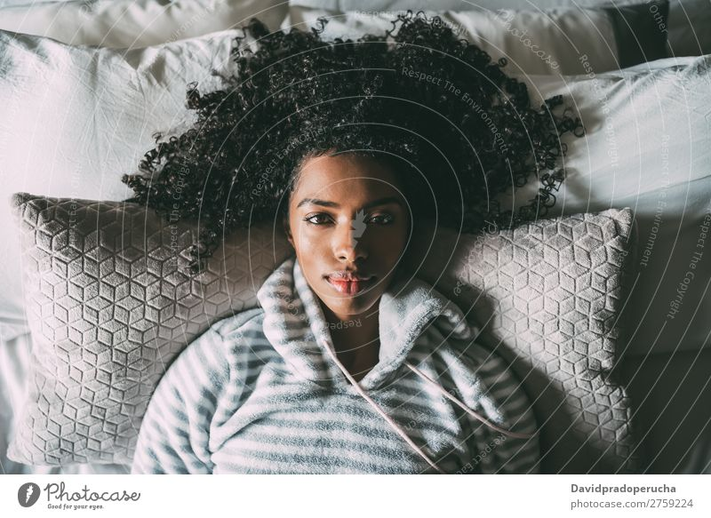 Beautiful black woman with curly hair lying on bed looking at the camera Woman Bed Black African pretty Bird's-eye view Close-up Curly hair Interior shot