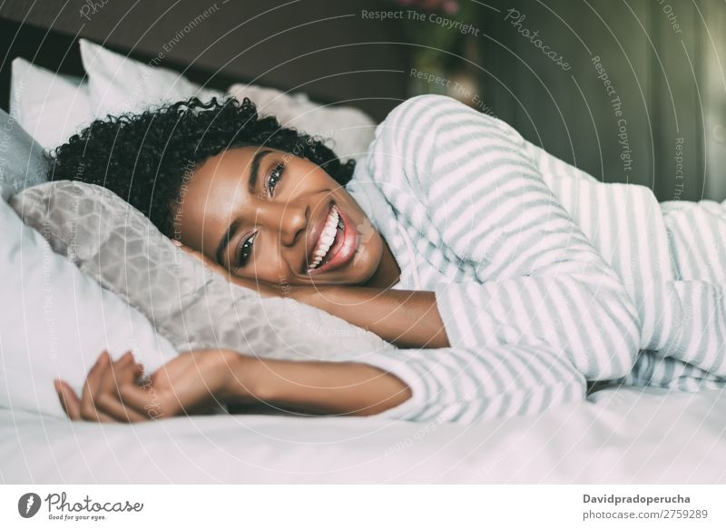 close up of a pretty black woman with curly hair smiling and lying on bed looking at the camera Woman Bed Portrait photograph Close-up Lie (Untruth) Black