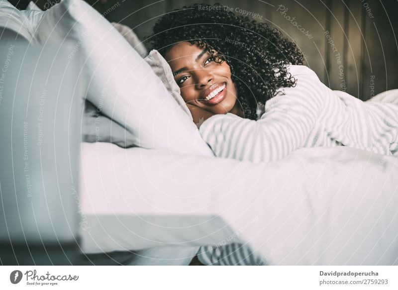 close up of a pretty black woman with curly hair smiling and lying on bed looking away Woman Bed Portrait photograph Close-up Lie (Untruth) Black Smiling