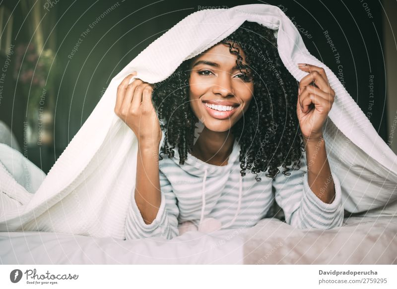 close up of a pretty black woman with curly hair smiling and covering with sheets on bed looking at the camera Woman Bed Sheet Portrait photograph Close-up