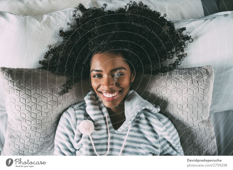 Beautiful black woman with curly hair smiling and lying on bed looking at the camera Woman Bed Black Smiling African Bird's-eye view