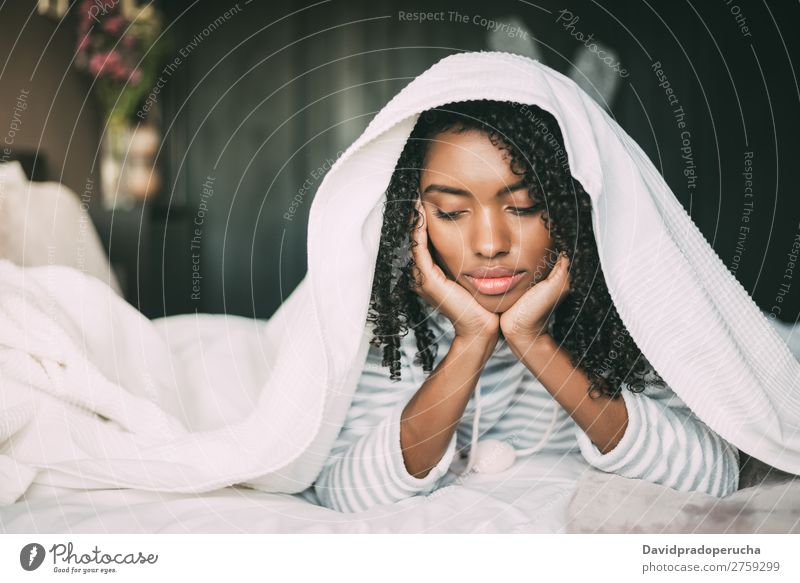 Beautiful serious thoughtful and sad black woman covering her head with sheet in bed Woman Bed Sadness Anger Black worried trouble problems Covered Covering