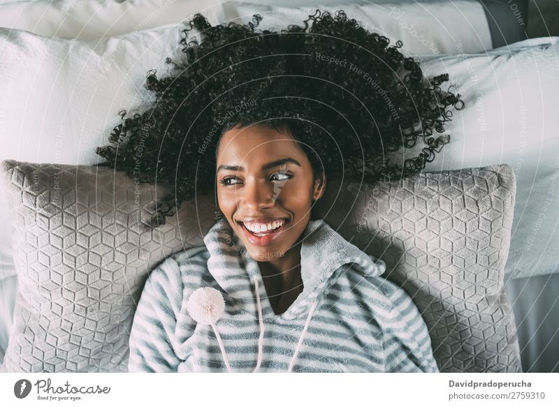 Beautiful black woman lying on bed looking at the camera smiling Woman Bed Black Considerate Smiling African pretty Bird's-eye view Close-up Curly hair