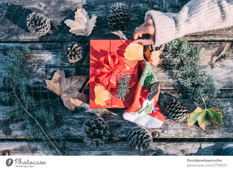 Woman arms doing christmas decoration in a wood table outdoors Christmas & Advent Gift Sock Santa Claus Life Still Life Background picture Decoration