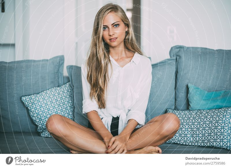 Portrait of a young thoughtful blonde woman sitting in the sofa Woman Sit Sofa Couch Portrait photograph Room Smiling Youth (Young adults) Considerate pretty