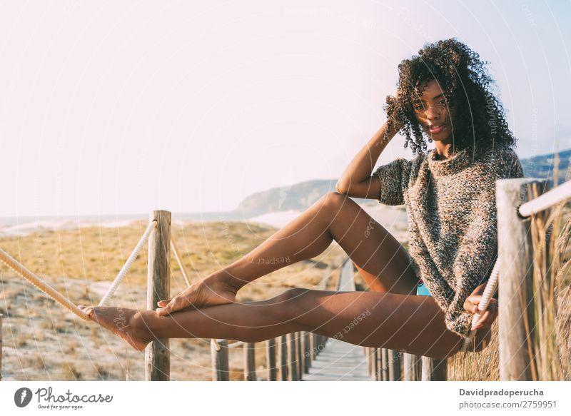 Beautiful young black woman sitting in a  wooden foot bridge at the beach Background picture Beach Bikini Black Bridge Coast Curly hair Destination Feet Hair