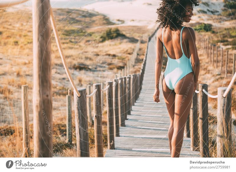 Young woman with a swimming suit walking in a wooden foot bridge at the beach Beach Woman Bikini Swimming Suit Black Bridge Background picture Coast Curly hair