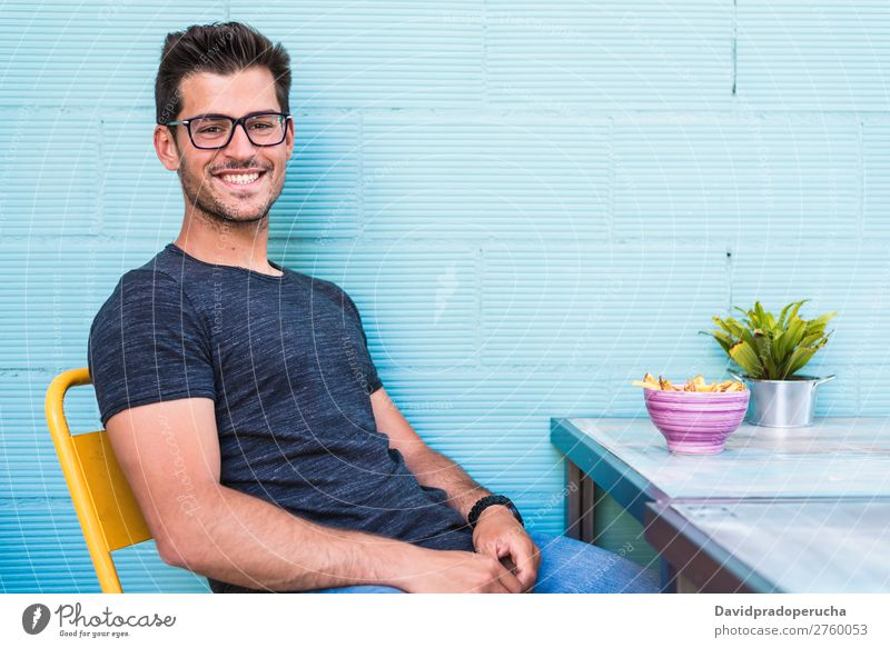 Happy young man seating in a restaurant Adults Loneliness Attractive Beautiful Blue Bright Caucasian Coffee Café Multicoloured enjoying Food Fries Guy handsome