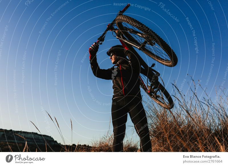 Cyclist holding the Bike at Sunset. Sports Lifestyle Relaxation Leisure and hobbies Adventure Summer Mountain Cycling Masculine Young man Youth (Young adults)