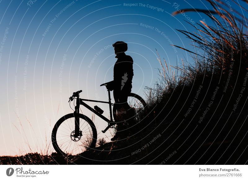 silhouette of a Cyclist with Bike at Sunset. Sports Lifestyle Relaxation Leisure and hobbies Adventure Summer Mountain Cycling Bicycle Masculine Young man
