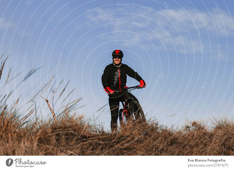 Cyclist Riding a Bike at Sunset. Sports Human being Sky Nature Youth (Young adults) Man Summer Young man Landscape Red Relaxation Joy Winter Mountain Black