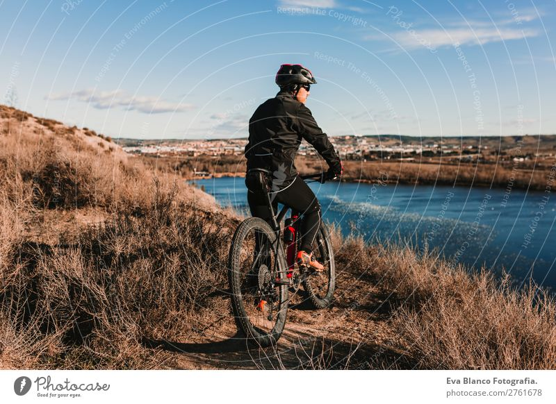 Cyclist Riding a Bike at sunset. Sports Lifestyle Relaxation Leisure and hobbies Trip Adventure Summer Sun Mountain Cycling Bicycle Masculine Young man