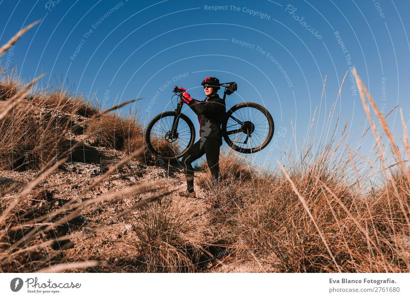 Cyclist Riding a Bike at sunset. Sports Human being Sky Nature Youth (Young adults) Man Summer Young man Landscape Red Sun Relaxation Joy Mountain Black