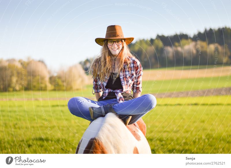 Young woman sitting cross-legged on a horse Lifestyle Joy Ride Vacation & Travel Feminine Youth (Young adults) 1 Human being 18 - 30 years Adults Landscape Sky