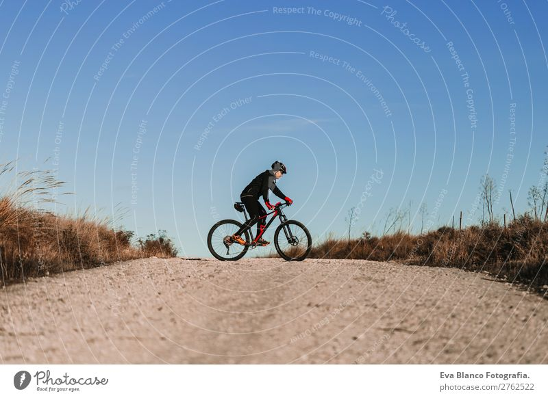 Cyclist Riding a Bike at dunset. Sports Lifestyle Leisure and hobbies Adventure Summer Sun Mountain Cycling Masculine Young woman Youth (Young adults) Man