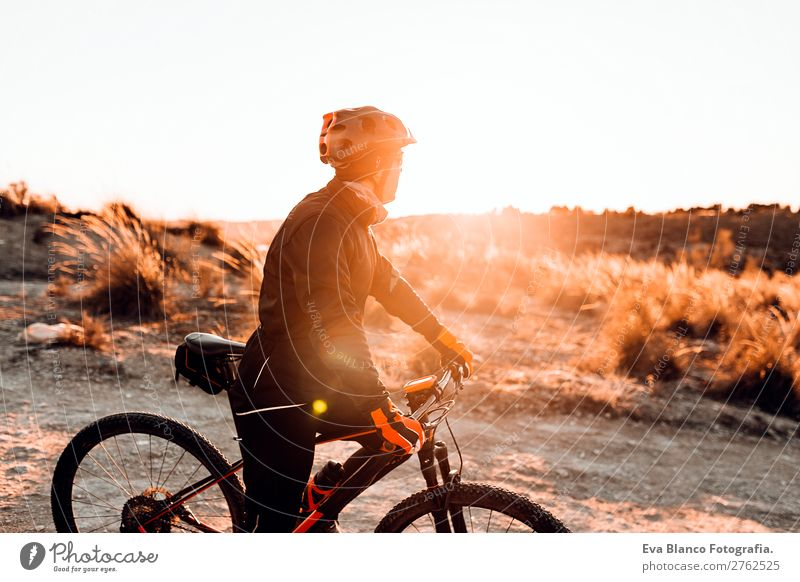 Cyclist Riding a Bike at dunset. Sports Lifestyle Relaxation Leisure and hobbies Adventure Summer Sun Mountain Cycling Bicycle Masculine Young man