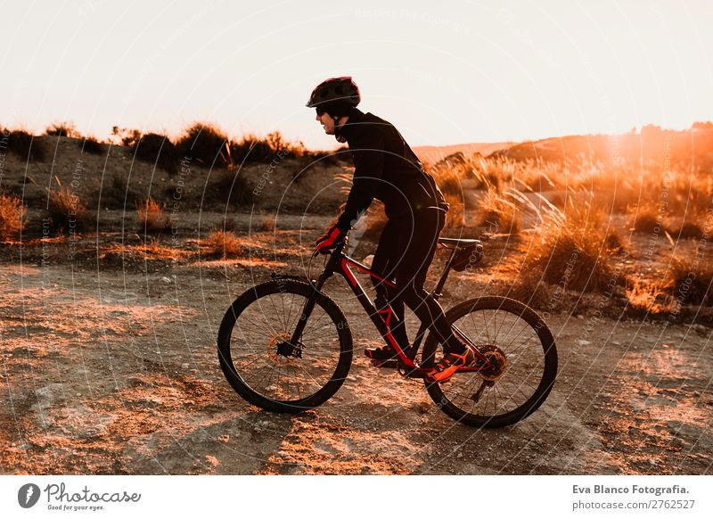 Cyclist Riding a bike at sunset. Sports Lifestyle Relaxation Leisure and hobbies Adventure Summer Sun Mountain Cycling Bicycle Masculine Young man