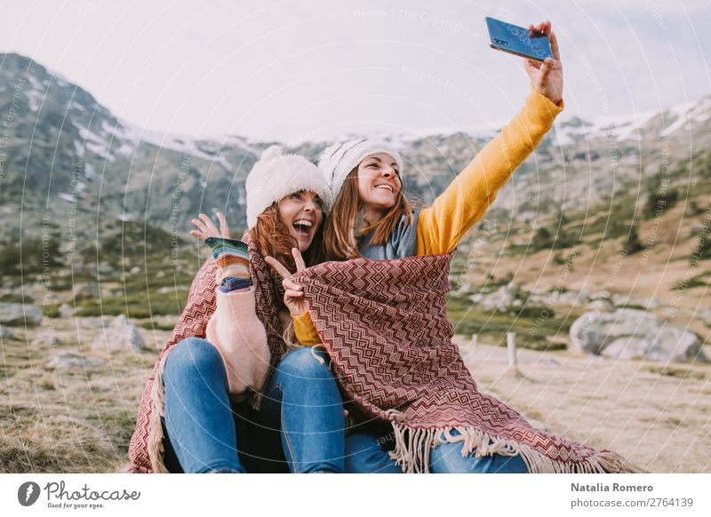 two girls are sitting in the meadow and take a photo Lifestyle Joy Happy Beautiful Vacation & Travel Tourism Adventure Freedom Mountain Hiking Telephone