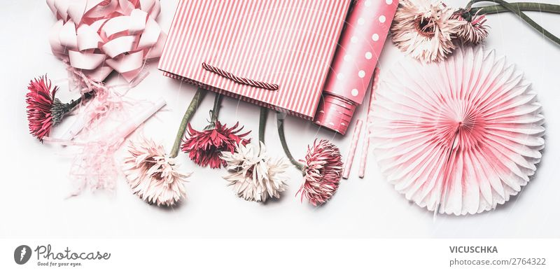 Composition of pink accessories to female holidays: Mothers day , Womens day, birthday or wedding. Paper shopping bag with flowers,paper, party fan and ribbon on white background, top view