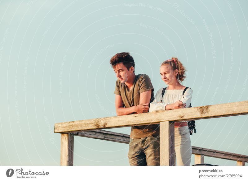 Smiling young woman and man sitting on a pier over the sea Lifestyle Joy Happy Leisure and hobbies Vacation & Travel Summer Ocean Human being Boy (child) Couple