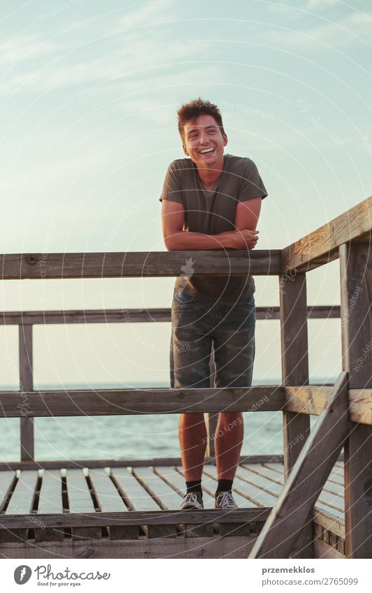Smiling happy young man standing on a pier over the sea Lifestyle Joy Happy Leisure and hobbies Vacation & Travel Summer Ocean Human being Boy (child)