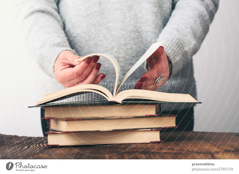 Woman turning pages of book on table in antique bookstore Lifestyle Shopping Relaxation Leisure and hobbies Reading School Study Human being Adults