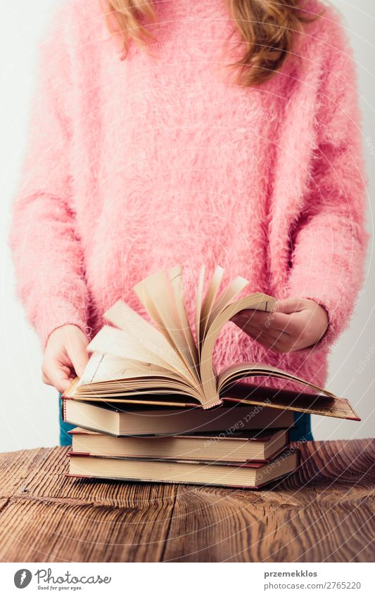 Young girl turning the pages of book in library Lifestyle Relaxation Leisure and hobbies Reading School Study Human being Woman Adults Youth (Young adults) Book