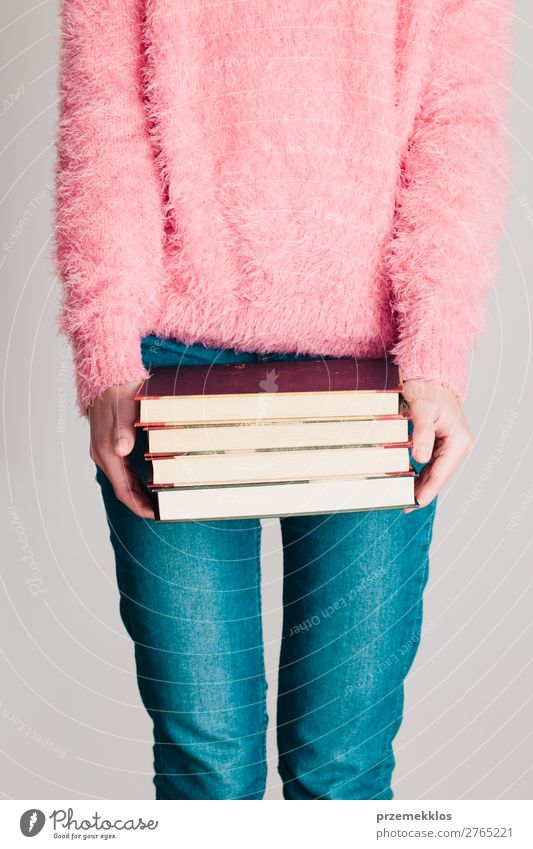Young girl holding a few books Lifestyle Relaxation Leisure and hobbies Reading School Study Human being Woman Adults Youth (Young adults) 1 Book Library