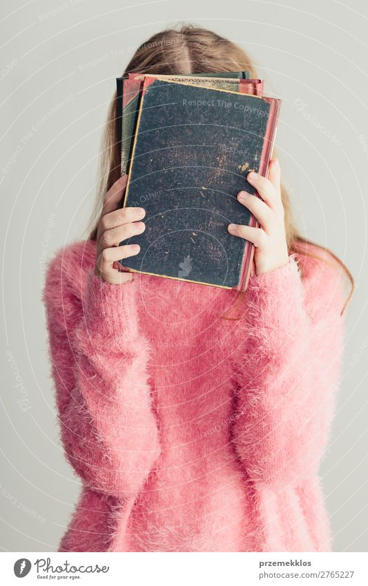 Young girl holding books in front of her face Lifestyle Joy Relaxation Leisure and hobbies Reading School Study Human being Woman Adults Youth (Young adults) 1