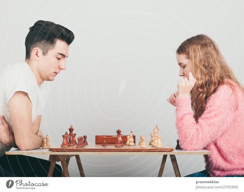 Girl and boy playing chess at home Lifestyle Leisure and hobbies Playing Chess Success Human being Boy (child) Woman Adults Man To enjoy Smart Black White