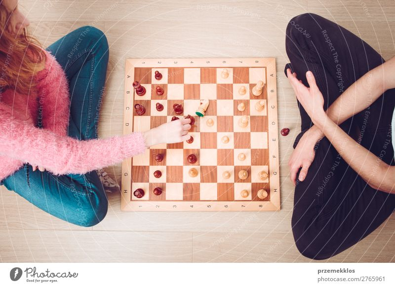 Girl and boy playing chess at home. Lifestyle Leisure and hobbies Playing Chess Success Human being Boy (child) Woman Adults Man To enjoy Smart Black White
