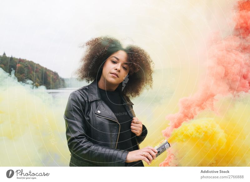Young woman with colored smoke bombs - a Royalty Free Stock