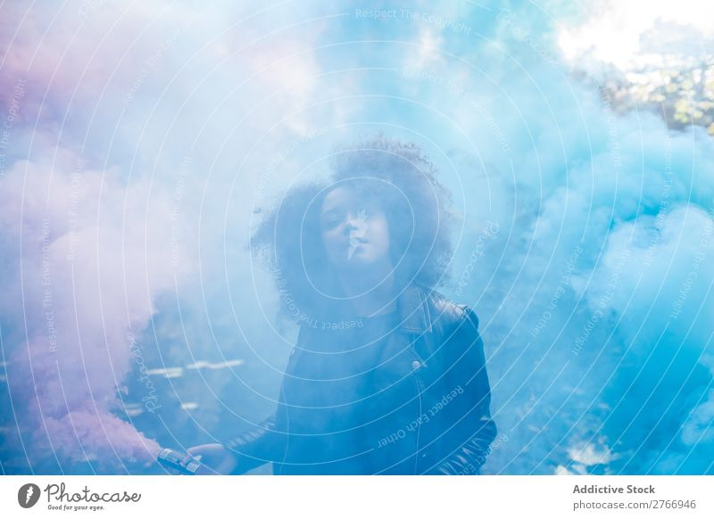 Young woman with colored smoke bombs - a Royalty Free Stock Photo