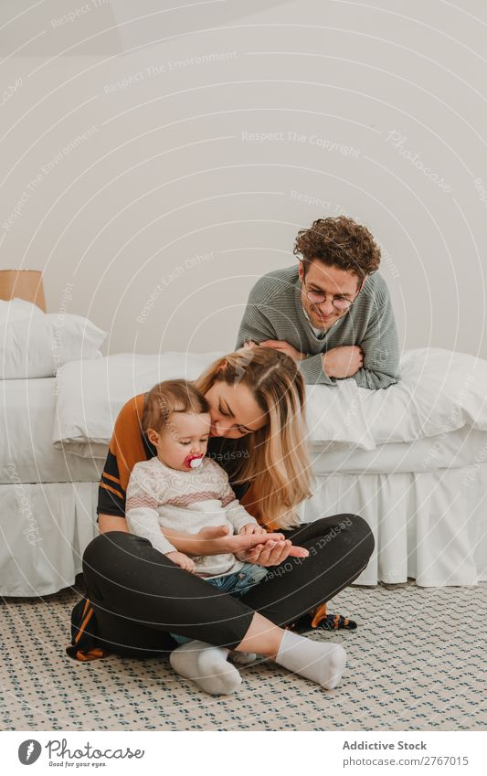 Cheerful couple with child on bed Family & Relations Mother Father Child Playing Human being Hotel Room Bedroom Home Interior design Furniture Flat (apartment)