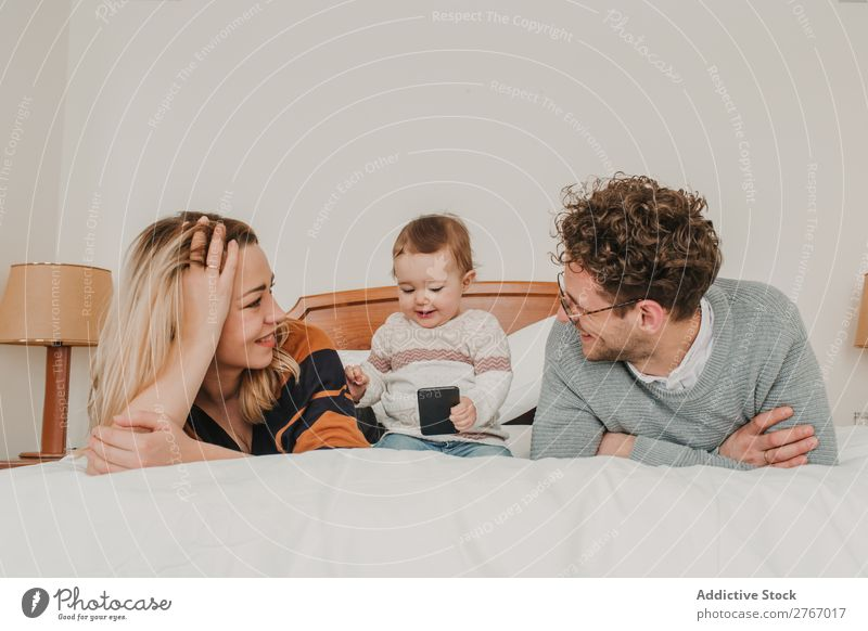 Cheerful couple with child on bed Family & Relations Mother Father Child PDA Playing Human being Hotel Room Bedroom Home Interior design Furniture