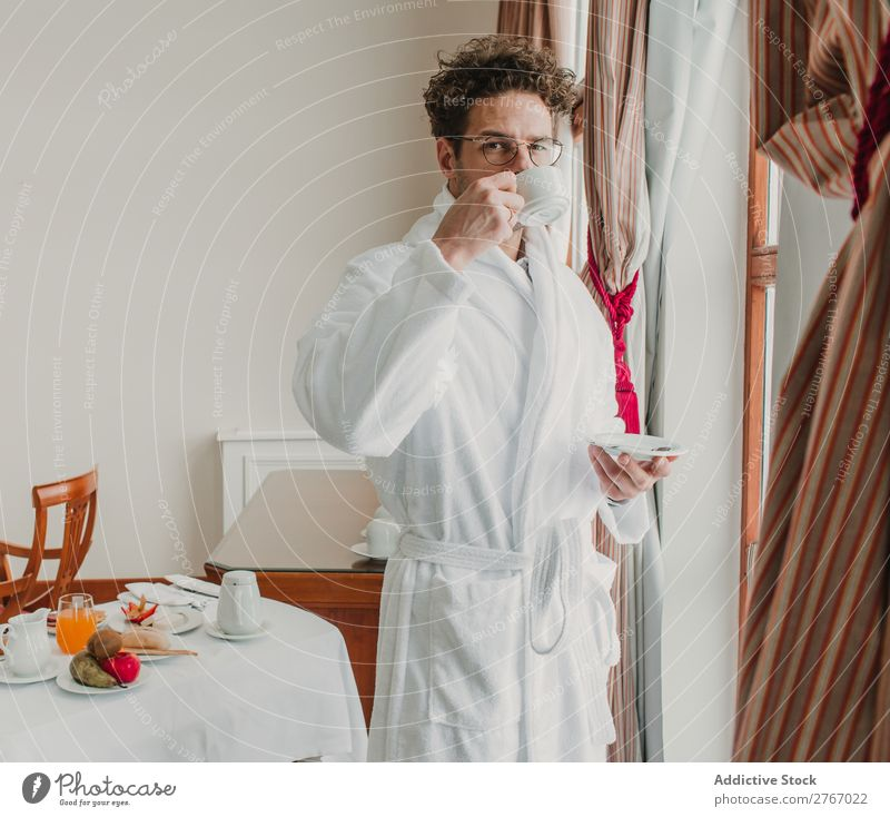Man in bathrobe with cup Bathrobe Self-confident Style ceramic Cup Window Drinking Breakfast Room service Hotel Bedroom Home Interior design Furniture