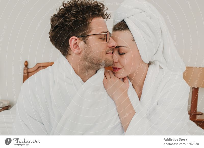 Happy couple embracing on bed Couple Bathrobe Cuddling eyes closed Hotel Room Bedroom Home Interior design Furniture Flat (apartment) Design Comfortable